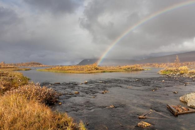 Arco-íris sobre o rio nas montanhas do ártico de um parque nacional de sarek.