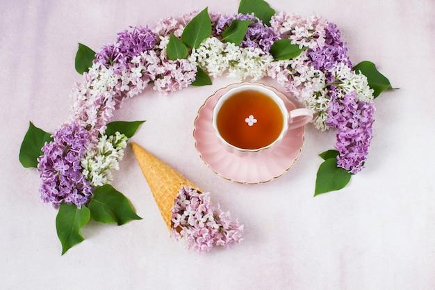 Arco lilás, uma xícara de chá e um ramo de lilás em um cone de waffle para sorvete