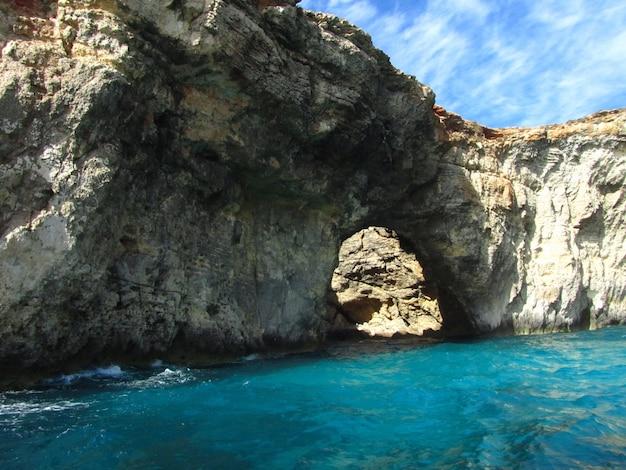 Arco natural rodeado pelo mar sob a luz do sol durante o dia em comino em malta