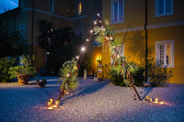 Arco para a cerimônia de casamento à noite em forma de cabana triangular decorada com flores e lâmpadas.