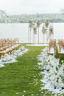 Arco premium para cerimônia de casamento de recém-casados na margem do rio com árvores de glicínias. cadeiras vazias e guarda-chuvas
