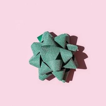 Arco verde brilhante de fita brilhante com sombra escura no papel rosa.