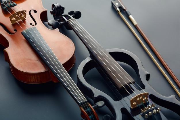 Arco, violino retrô de madeira e viola elétrica moderna, vista do close up, ninguém. dois instrumentos musicais de cordas clássicas