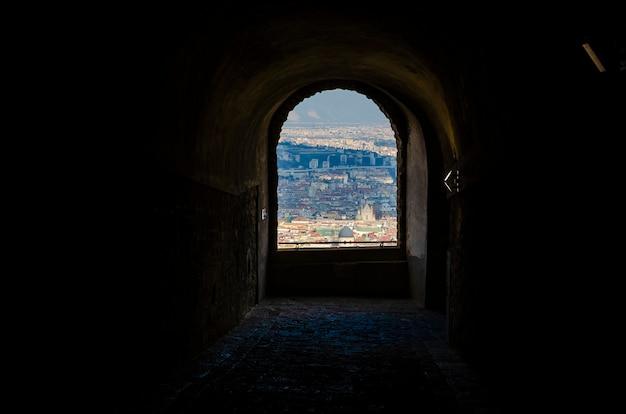 Arco vista para a cidade do antigo castelo em nápoles, itália (castel sant'elmo). paisagem urbana e o conceito de arquitetura antiga