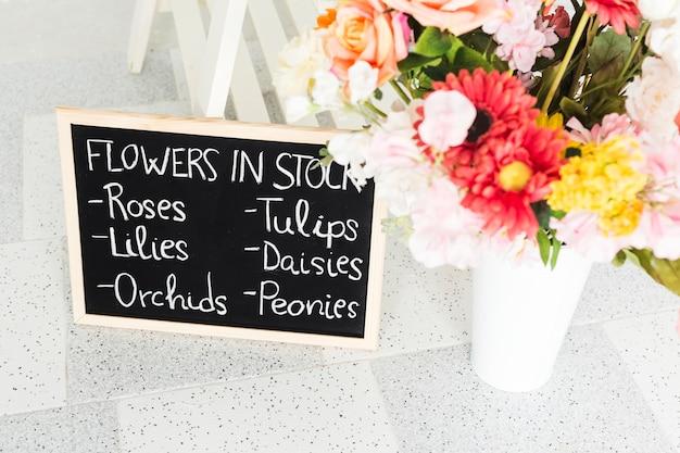 Ardósia com nomes de flores perto de vaso no chão