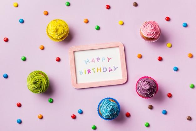 Ardósia de feliz aniversário rodeada de gemas coloridas e muffins em fundo rosa