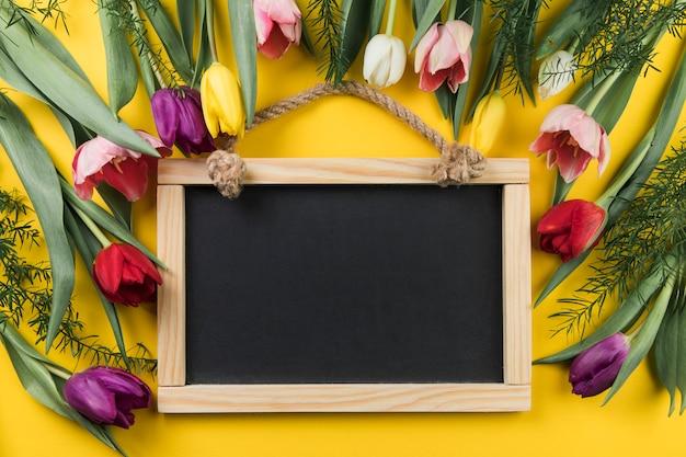 Ardósia de madeira em branco decorado com tulipas frescas coloridas contra fundo amarelo
