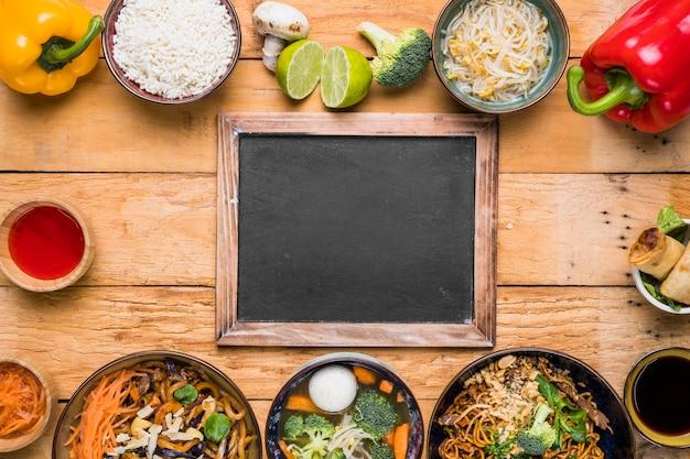 Ardósia em branco com comida tailandesa tradicional na mesa de madeira