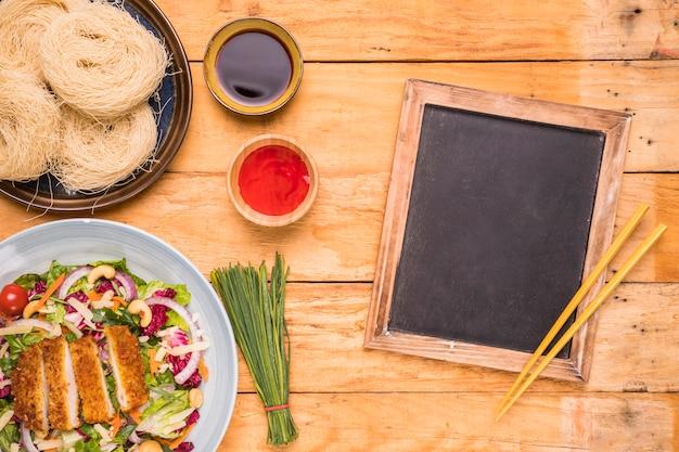 Ardósia em branco com pauzinhos e comida tradicional tailandesa na mesa de madeira