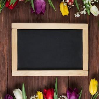 Ardósia em branco de madeira com tulipas coloridas dispostas na borda superior e inferior sobre o fundo de madeira