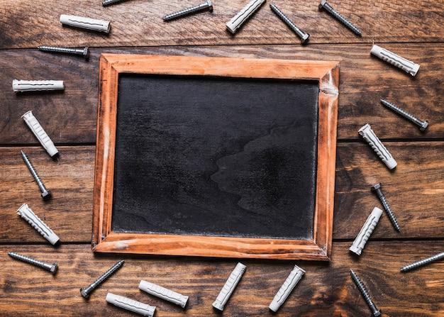 Ardósia preta em branco, rodeada por vários parafusos no fundo de madeira