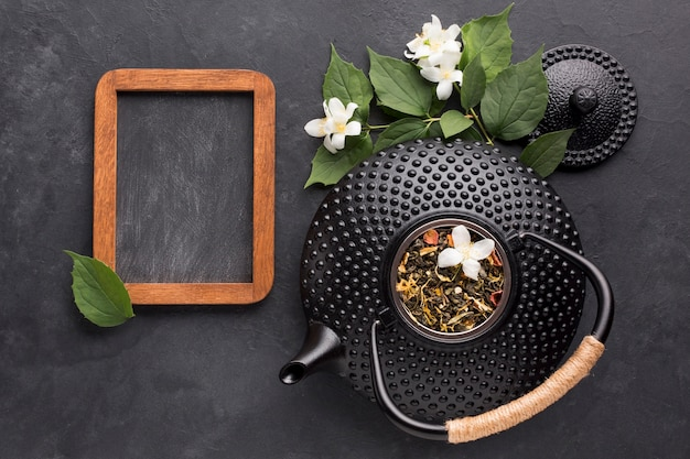 Ardósia vazia preta com ingrediente de chá seco em fundo preto