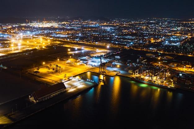 Área da fábrica e terminal de transporte porta do recipiente de carga de importação e exportação à noite