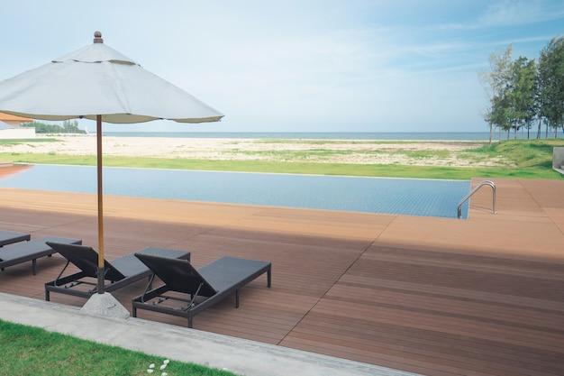 Área da piscina com espreguiçadeiras, espreguiçadeiras e guarda-sol no hotel resort de praia.