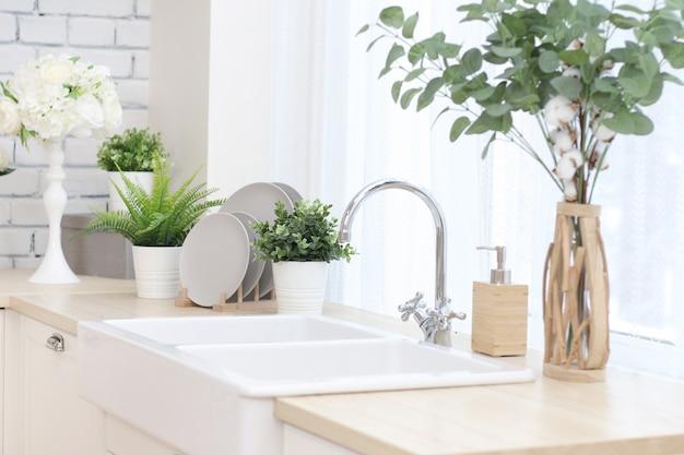 Área de cozinha com flores artificiais em vasos, pratos em um carrinho de madeira, uma pia grande com uma torneira.