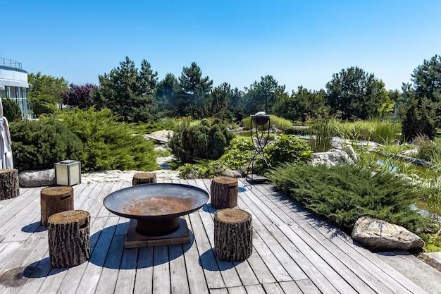 Área de estar ao ar livre com churrasqueira e tocos de madeira no quintal de uma propriedade rural no verão