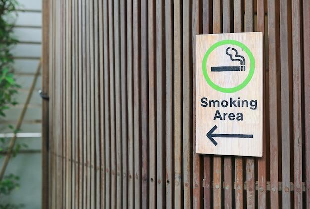 Área de fumar com seta na placa de madeira na parede de prancha de madeira com espaço de cópia.