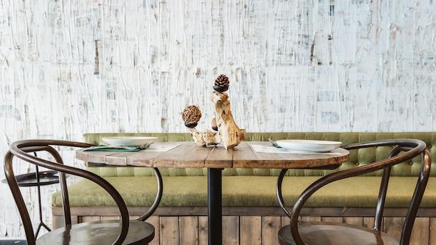 Área de jantar decorada com sofá verde, mesa de madeira, cadeira de aço preta e papel de parede branco com textura de arranhões. atmosfera de restaurante interior moderno.