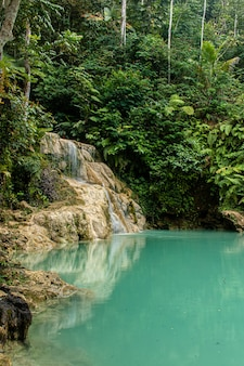 Área de natação vazia de água turquesa com a cachoeira mudal