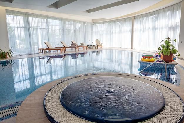 Área de relaxamento perto da piscina coberta com jacuzzi e espreguiçadeiras em uma mansão de campo