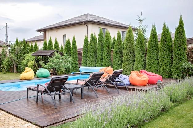 Área de spa no quintal de casa na piscina de verão, cadeira macia colorida brilhante, férias felizes