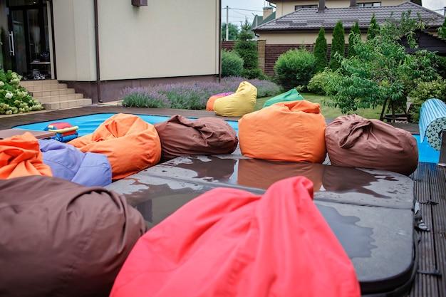 Área de spa no quintal de casa na piscina de verão, cadeira macia colorida brilhante, férias felizes Foto Premium