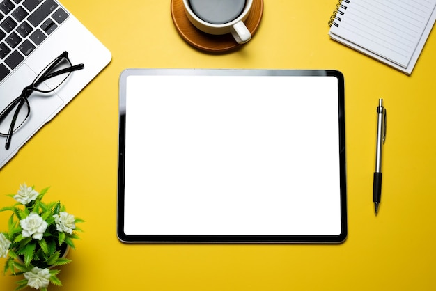 Área de trabalho amarela de vista superior com caderno de óculos de teclado de café de tela branca em branco tablet colocado sobre a mesa.