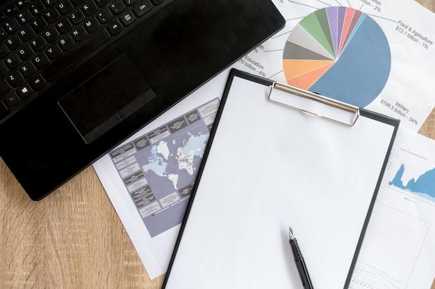 Área de trabalho arrumada do empresário e ferramentas de trabalho com papelada, computador, dispositivos de tela de toque e papelaria em uma superfície de madeira, vista superior