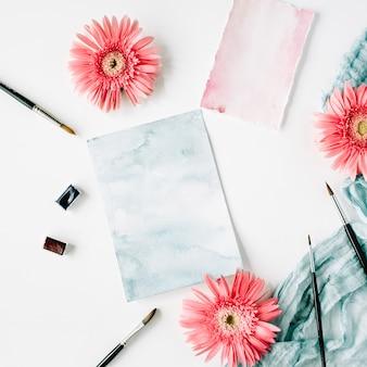 Área de trabalho. botões de gerbera rosa e papel aquarela com pincel e tecido azul no branco