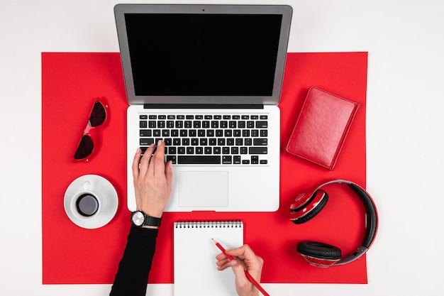Área de trabalho com laptop, fones de ouvido, calculadora, canetas, lápis, cartão, telefone isolado em fundo preto e branco