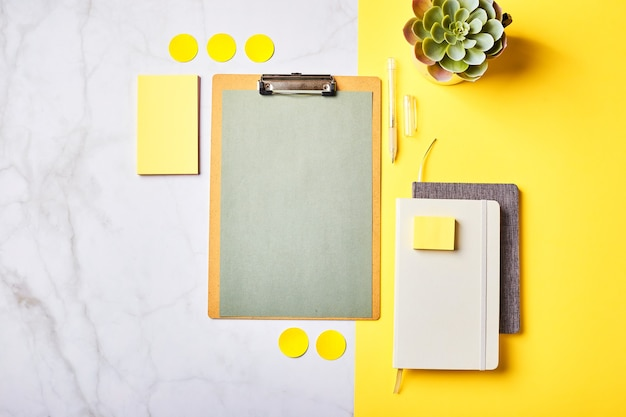 Área de trabalho com maquete de área de transferência e material de escritório. escritório em casa, planejando o conceito de definição de metas. flatlay, vista superior