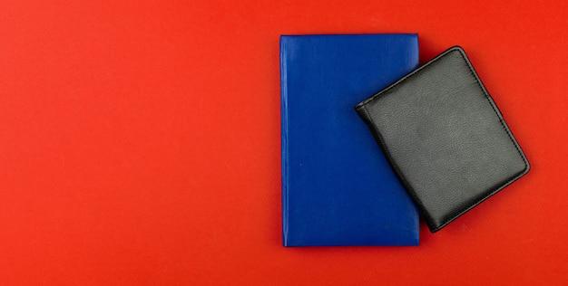 Área de trabalho com maquete de cadernos de couro preto e azul, fundo vermelho com espaço de cópia, foto do conceito de design moderno