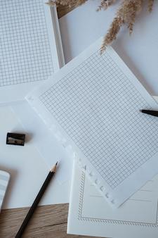 Área de trabalho da mesa do escritório doméstico com folhas de papel em branco, caderno, grama dos pampas na madeira
