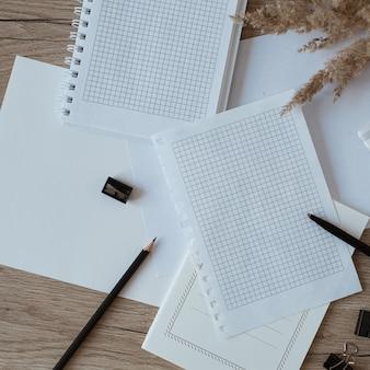 Área de trabalho da mesa do escritório doméstico com folhas de papel em branco, caderno, grama dos pampas