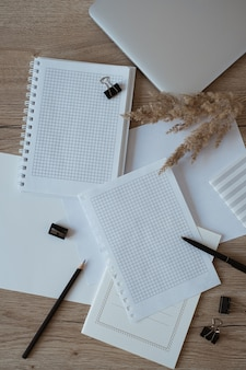 Área de trabalho da mesa do escritório doméstico com folhas de papel em branco, laptop, caderno, grama dos pampas