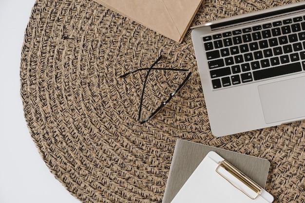 Área de trabalho da mesa do escritório doméstico com laptop, área de transferência, óculos em fundo de vime de palha