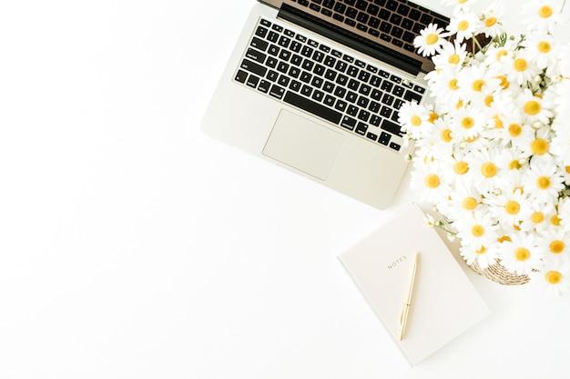Área de trabalho da mesa do escritório doméstico com laptop, buquê de camomila e caderno na superfície branca