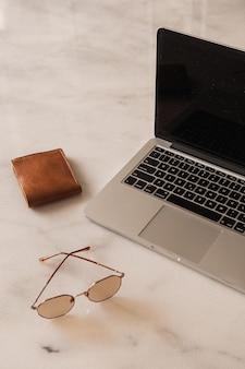 Área de trabalho da mesa do escritório doméstico com laptop, óculos de sol, carteira na mesa de mármore