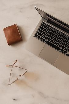 Área de trabalho da mesa do escritório doméstico com laptop, óculos e carteira na mesa de mármore