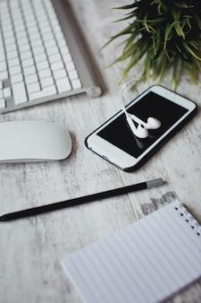 Área de trabalho da mesa do escritório em casa com fones de ouvido, smartphone e teclado