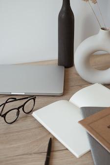 Área de trabalho da mesa do escritório em casa com laptop, notebook, óculos de madeira