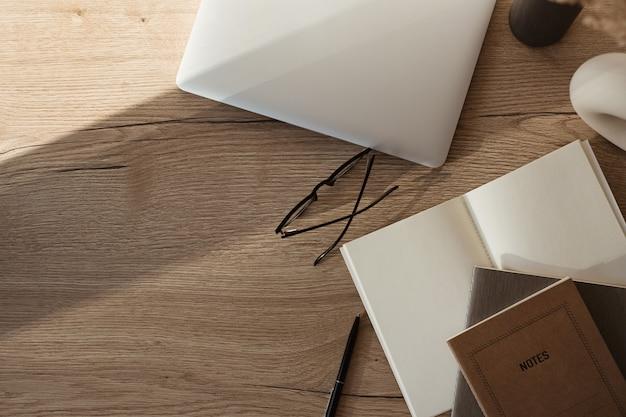 Área de trabalho da mesa do escritório em casa com laptop, notebook, óculos, sombras de luz solar