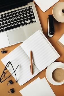 Área de trabalho da mesa do escritório em casa com laptop, xícara de café, caderno de folha em branco, óculos, caneta, ramo de planta verde em gengibre