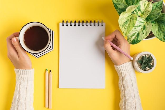 Área de trabalho das mãos de uma mulher escrevendo no bloco de notas em branco