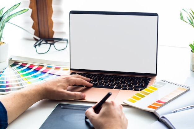 Área de trabalho de design gráfico com maquete de laptop de tela em branco