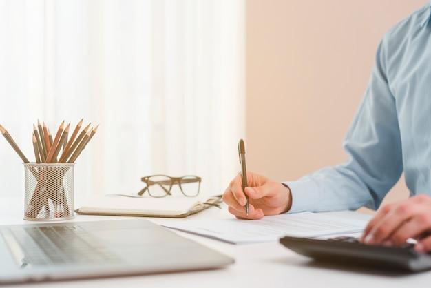 Área de trabalho de escritório com laptop e um homem de negócios