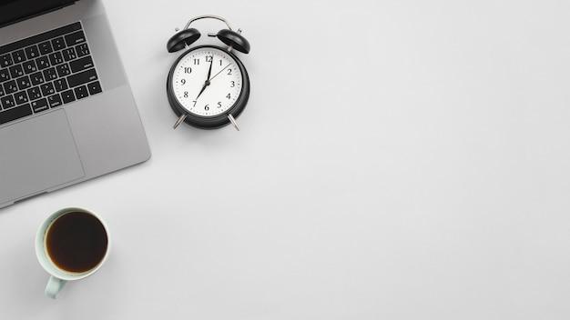 Área de trabalho de escritório com laptop e um relógio