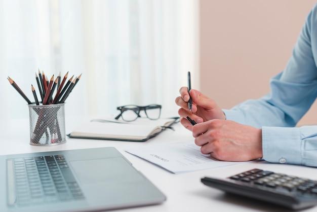 Área de trabalho de escritório com laptop e uma calculadora