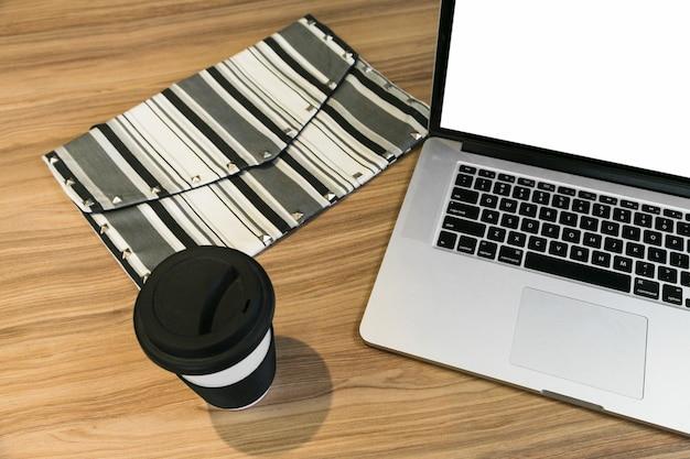 Área de trabalho de escritório com laptop e uma xícara de café