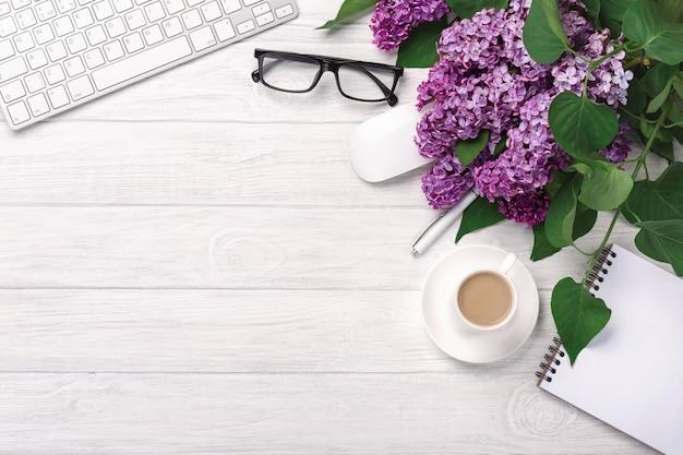 Área de trabalho de escritório com um buquê de lilases, xícara de café, teclado, caderno e caneta em quadros brancos